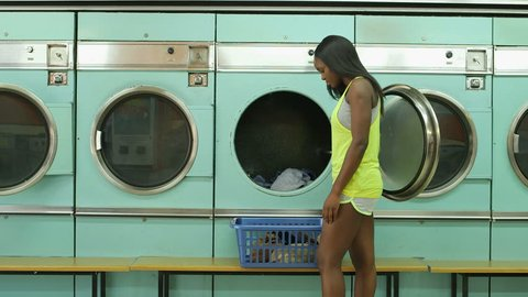 A Young Woman tosses her clothes into a washing machine and waits in the Launderette