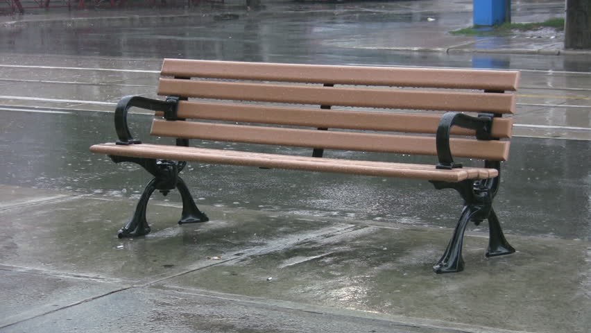 Bench in the rain. A city bench getting wet during a summer thunderstorm. Toronto, Ontario, Canada.