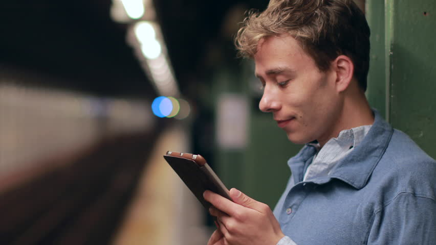 Young caucasian man in New York City subway station platform using tablet pc computer | Shutterstock HD Video #6463031