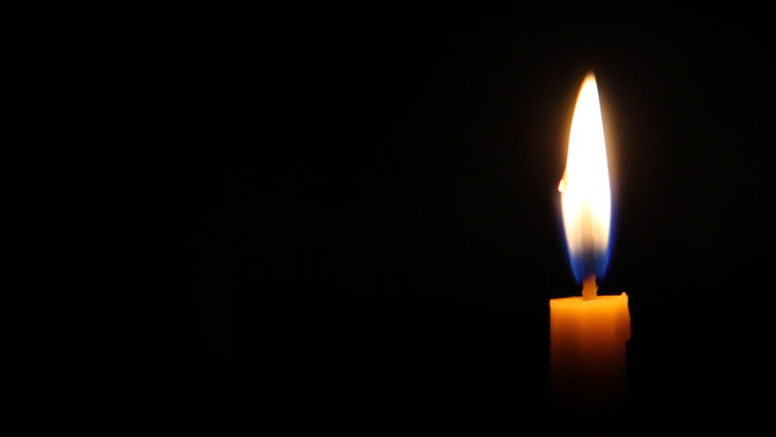 Looping of candle with flickering flame shining in darkness