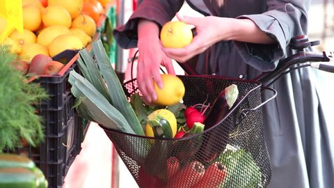 Close up of a bike with basket, full of fruit and vegetables