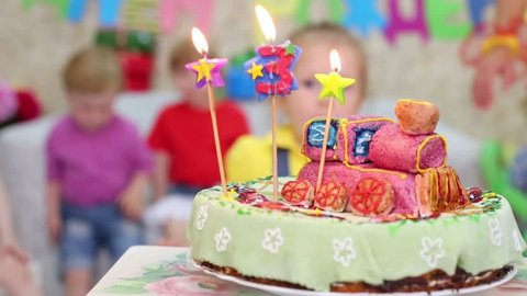 Birthday Cake With Three Candles Is On Table And Five Kids Expect Treats At Children Party