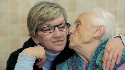 daughter consoling his mother who is alone sad and depressed: aged, old, ancient