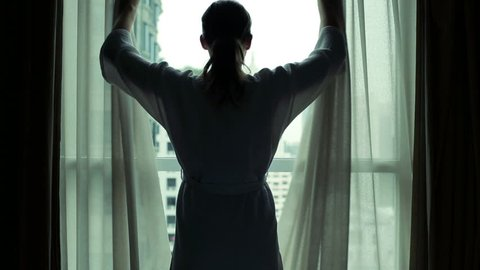 Woman unveil curtains in hotel room, view at amazing cityscape