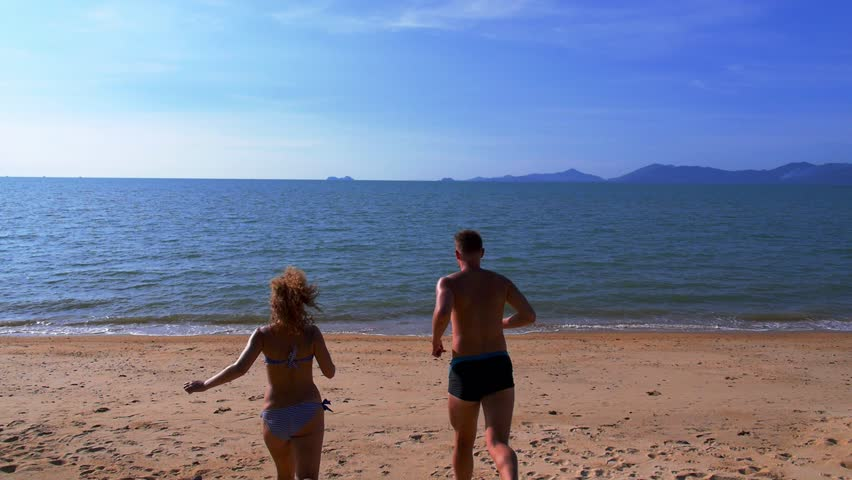 Happy Couple Running on a Sandy Beach and Dive in Blue Tropical Sea. Koh Samui. Thailand.