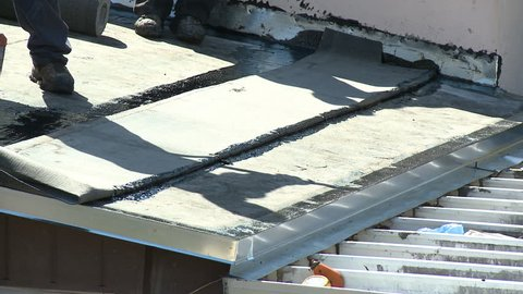 Flat roof installation - roofers applying bitumen with a mop to lay down final membrane