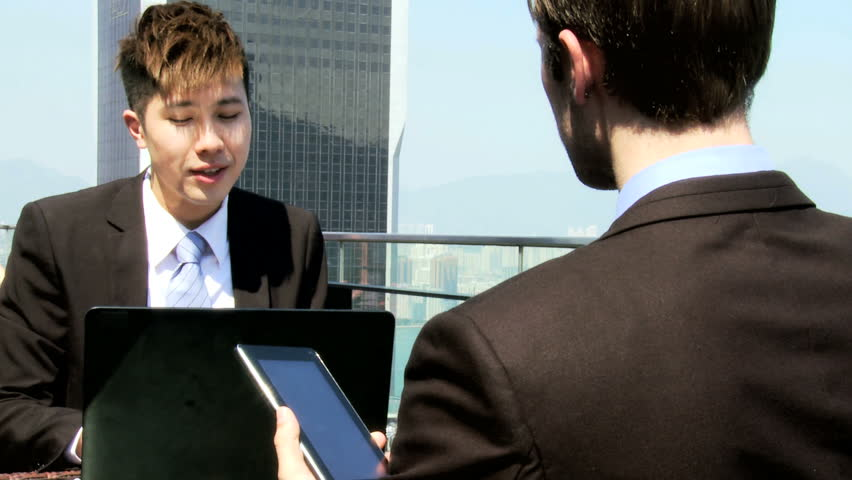 Male multi ethnic corporate city people smart business clothes meeting using spreadsheets wireless tablet laptop technology outdoors downtown rooftop | Shutterstock HD Video #6645302