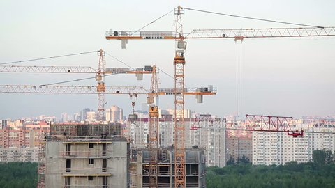 """SAINT-PETERSBURG, RUSSIA - CIRCA JUNE, 2014: Several cranes are over building under construction. New sleeping district """"Baltic Pearl"""" is in south of city."""