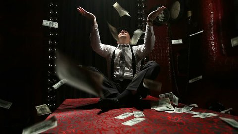 Italian gangster sitting on a table scatters packs of dollars. Rain of banknotes.
