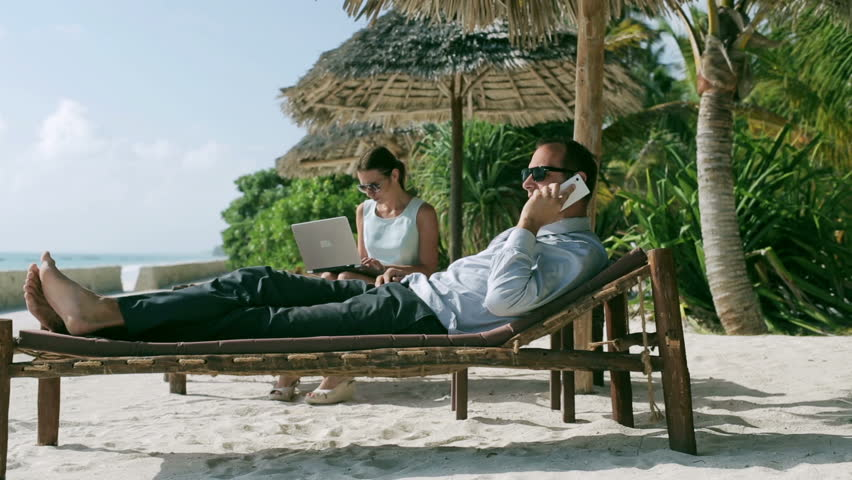 Businesspeople working on sunbed in exotic place