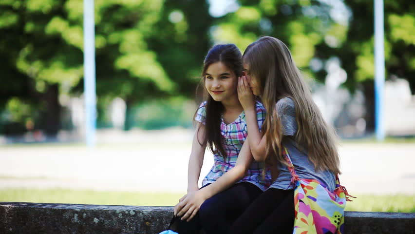 Two little girls whispering secrets while sitting outdoors full hd two little girls whispering secrets while sitting outdoors full hd photo jpeg hd stock voltagebd Image collections