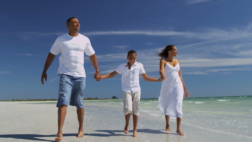 Loving Young Ethnic Family Skipping Ocean Shallows - Young attractive ethnic parents son dressed in white enjoying beach vacation playing on beach together shot on RED EPIC | Shutterstock HD Video #6685748