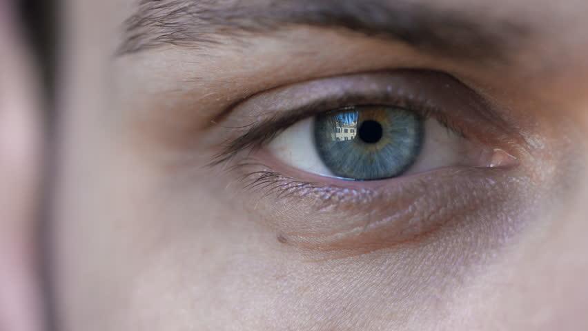 intense gaze: blue eye in macro 4k footage of young handsome man