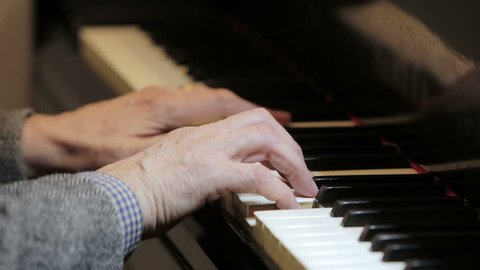 close up on hands playing piano: classical music, keys, score, musician, senior