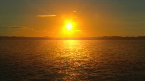 Sunset over the ocean. Timelapse sequence of sun setting as camera moves slowly over the ocean.
