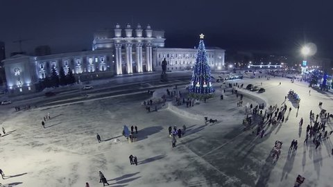 RUSSIA, SAMARA - JAN 6, 2014: People walk by Kuibyshev Square with christmas tree at winter evening. Aerial view. Kuibyshev Square is largest square in Europe.