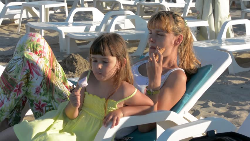 Young mother with daughter eating ice cream sea on the chair