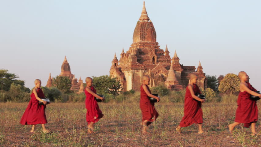Young Buddhist novice monks walk past a temple in procession carrying alms bowls / Bagan, Myanmar