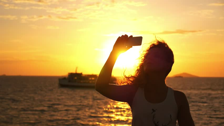 Attractive Young Woman with Curly Hair Taking Selfie against Impressive Sunset during Sea Cruise. Slow Motion. Thailand. Gulf of Siam.