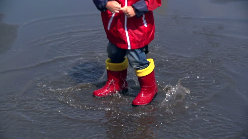 Unrecognizable child splashing water of the slop hopping in it