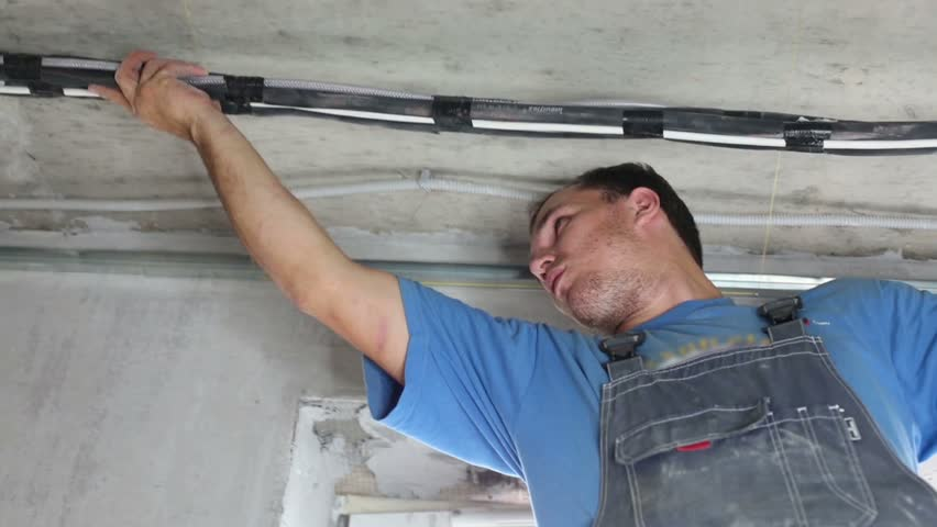 Young Worker Sets Tube On Ceiling For Air Conditioner In Apartment ...