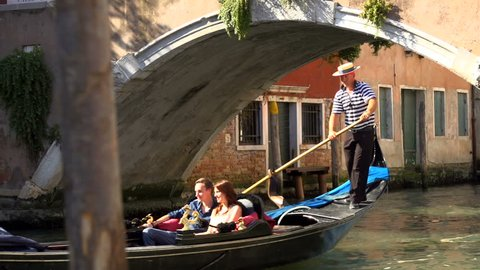 A young couple are punted along a Venice canal in a gondola