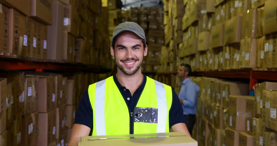 Warehouse worker smiling at camera carrying a box in a large warehouse worker smiling at camera carrying a box in a large warehouse stock footage video 6857572 shutterstock sciox Choice Image