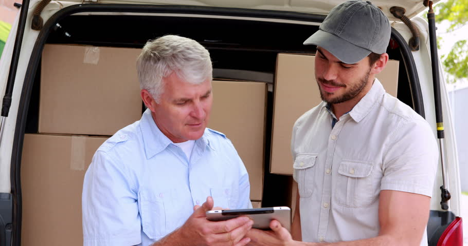 Delivery driver using tablet to take customers signature in a large warehouse