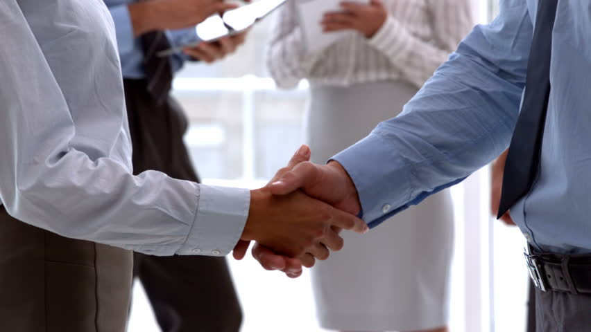 Business team shaking hands close up in slow motion