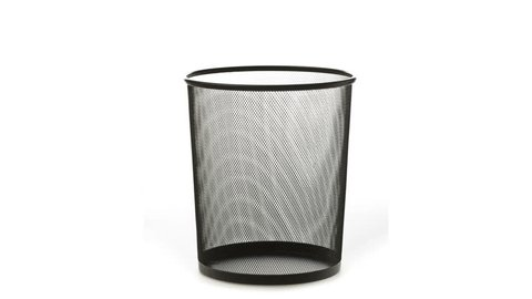 An empty office trash basket gets filled up with papers