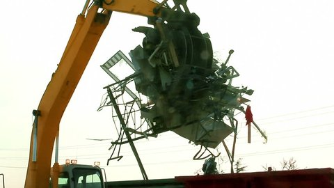 An excavator is loading scrap metal junk into a bin at a garbage dump or recycling center. Waste includes household appliances and roofing iron. Part 2 (joins part 1 with a 2 second overlap.)