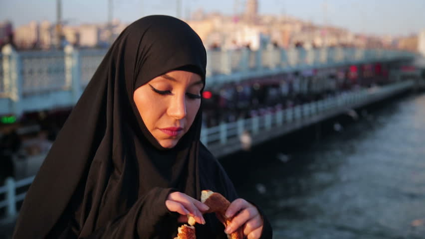 Woman dressed with black headscarf, chador eating simit, turkish bagel with istanbul city view, turkey