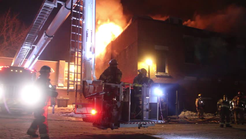 Montreal, Canada - February 2014 - Firetruck elevated platform rising with fire in background	A ladder platform linked to a fire truck with two firemen inside is rising slowly with building on fire