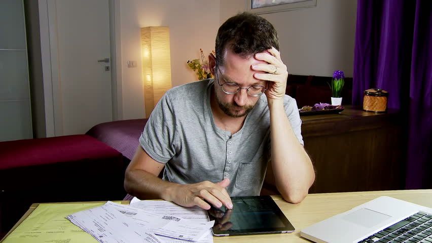 Man at home calculating bills and taxes with tablet calculator