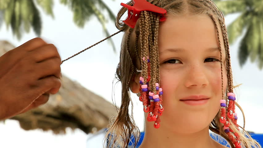 A Cute 9-year-old Girl Gets Her Hair Braided Outdoors At ...