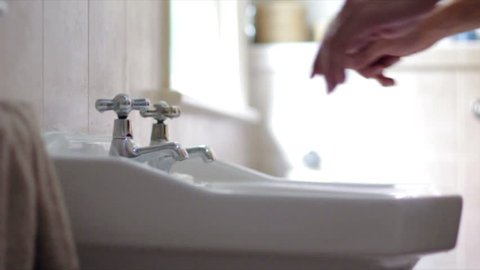 Young male freshens up by washing his hands and face in the sink of the bathroom, at half speed