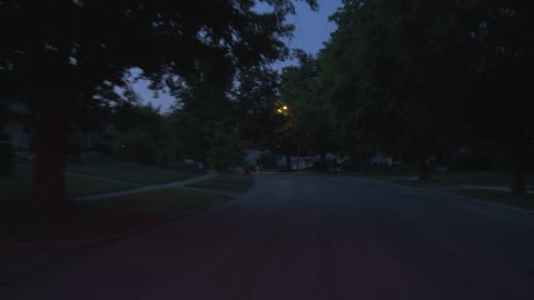Driving plate, rear view, night.  Tree-lined road through well-tended middle class suburban neighborhood with 1940s & 1950s era Cape Cods, bungalows and similar homes.  Recorded on Tyler Mini Gyro.