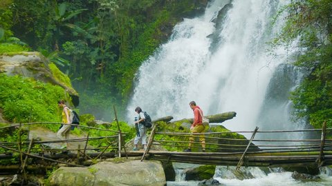 Video 1080p - Tourists cross the river on a background of a waterfall. Doi Inthanon National park. Thailand