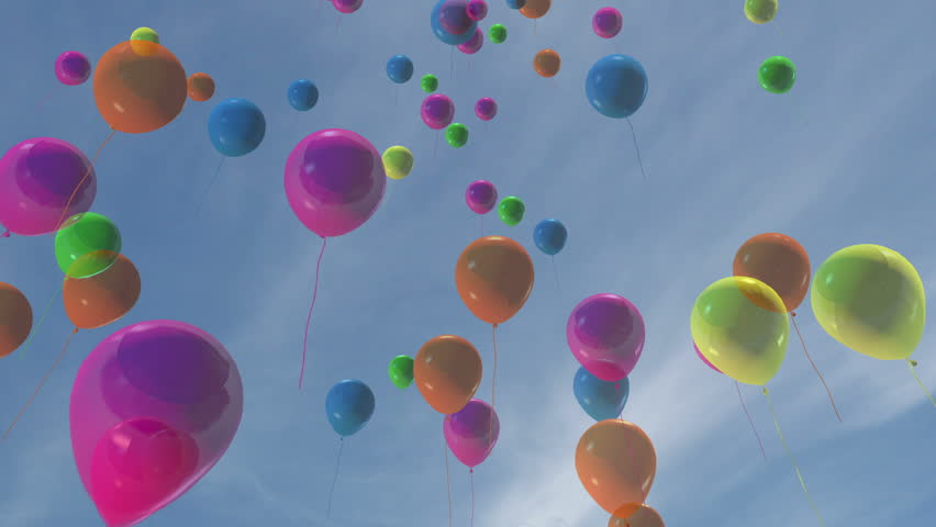 Multi-colored balloons floating up into a blue sky