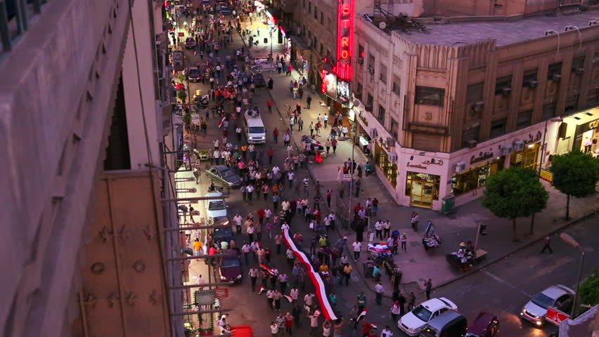Overhead view looking at an intersection as protestors march in the streets of Cairo, Egypt at night.