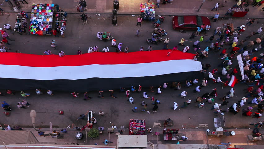 View from overhead looking straight down as protestors carrying banners march in the streets of Cairo, Egypt.