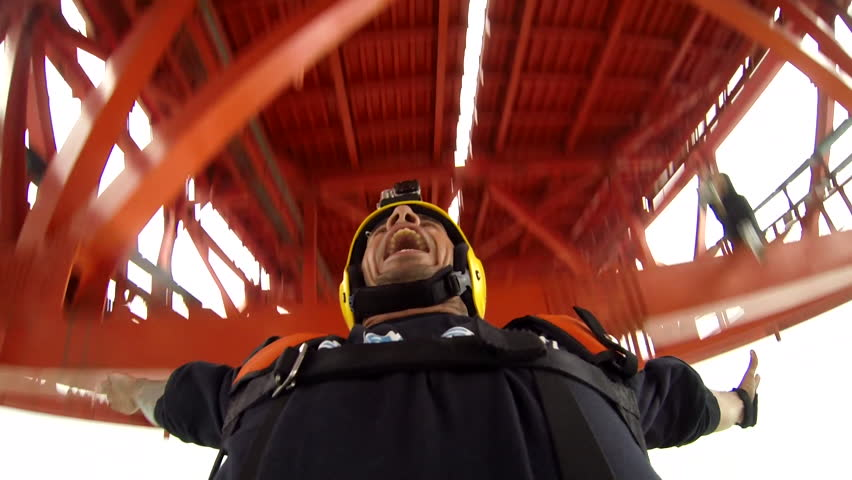 Close-up of a base jumper opening his parachute after jumping from a platform
