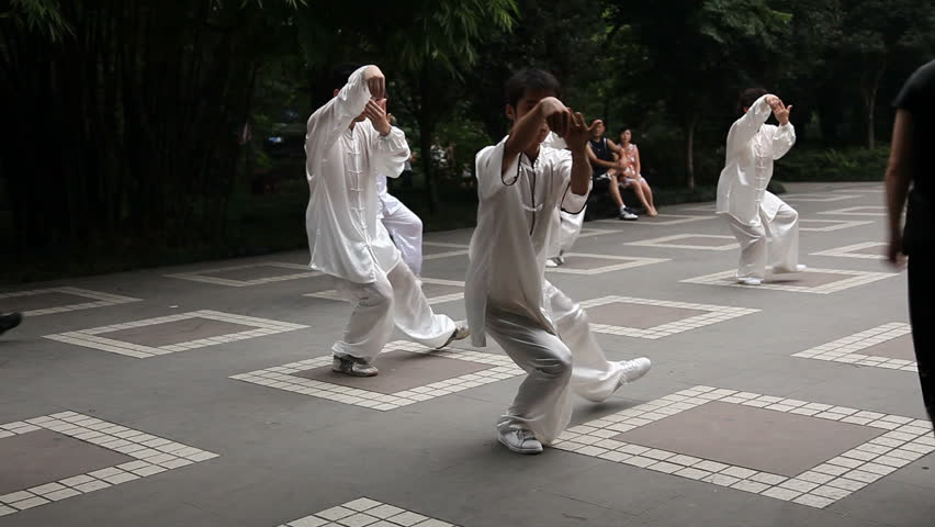 Chengdu, China - August 10: Chinese man and woman dressing white silk practice balancing Tai Chi in the People's Park daily - Chengdu, China in Sichuan Province, August 10, 2009