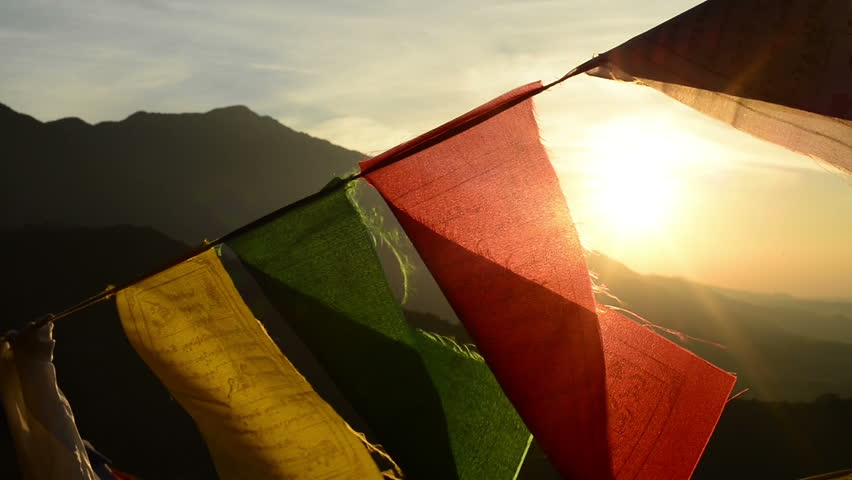 Tibetan buddhist prayer flags blowing in the wind. Sunrise at Himalayan foothills in India as a background.
