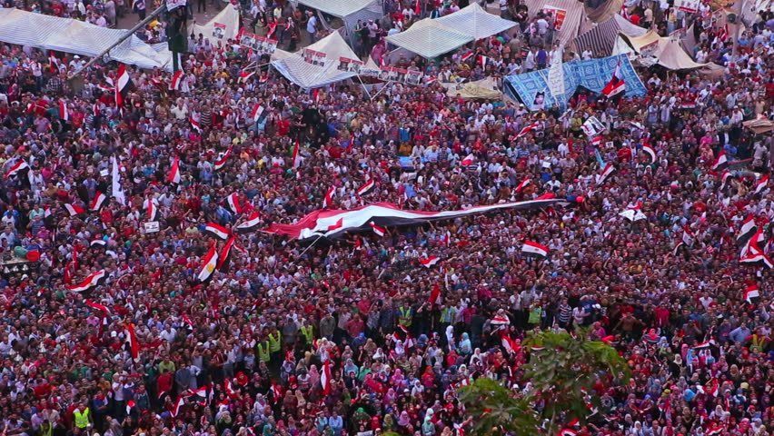 CAIRO, EGYPT - CIRCA 2013 - Overhead view as protestors wave flags and jam Tahrir Square in Cairo, Egypt.