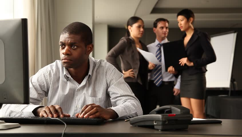 Male office worker sitting at her desk looking at camera with fed up expression and raising her hand in sign of desperation. Colleagues chattering and laughing in the background. Multi ethnic group.