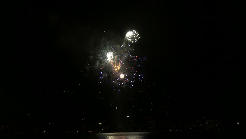 Colorful opening fireworks and reflections celebrating the summer over the lake at Suwa in Japan.