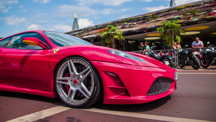VELDEN, AUSTRIA - JUNE 2014: Street show supercars. Very expensive cars driving through town. Red Ferrari in slow motion low angle passing by