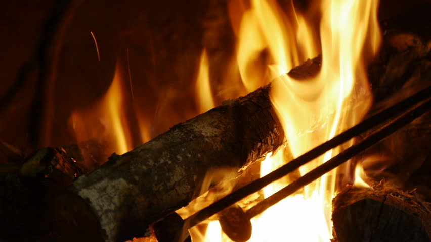 Man Wears Gloves, Uses Tongs To Turn Burning Logs, Keep Fire Going ...