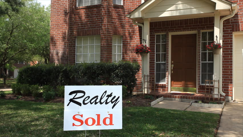 A sign in the front hard of a large brick house advertises that it has been SOLD.